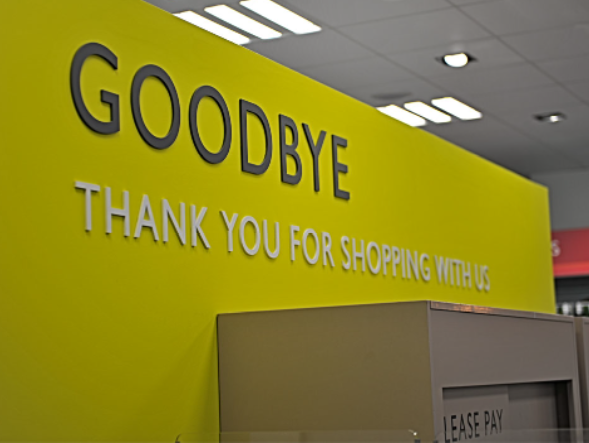 "Internal shot of Waitrose, yellow wall with grey sign ""Goodbye thank you for shaopping with us"""